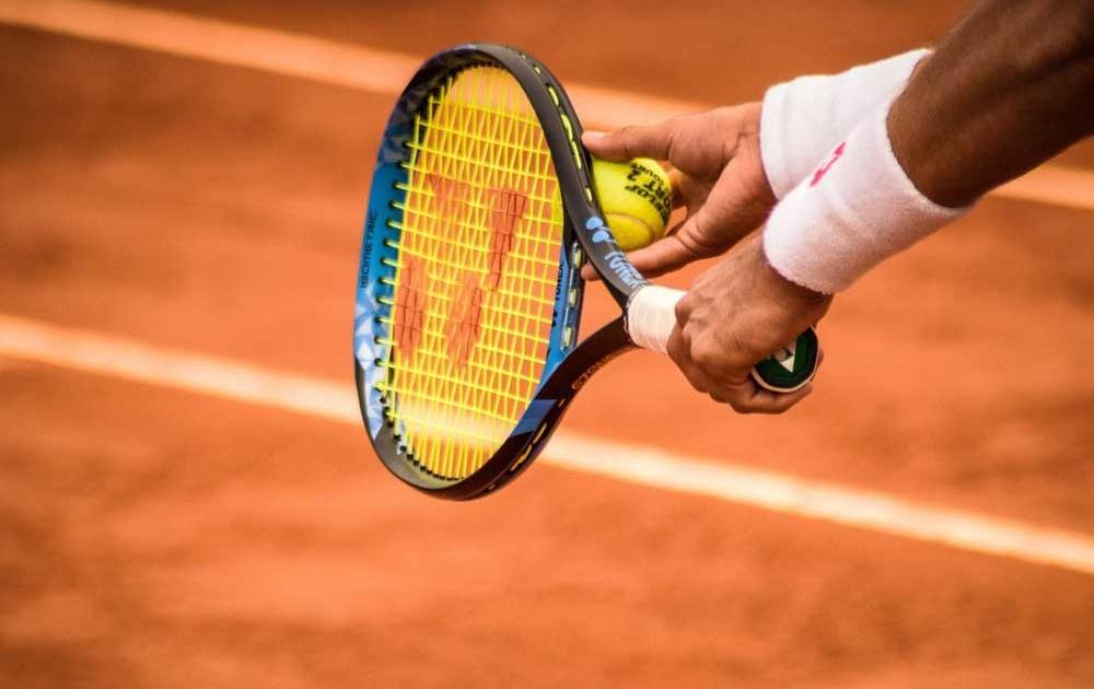 Hände mit Tennisschläger und Ball kurz vor dem Aufschlag